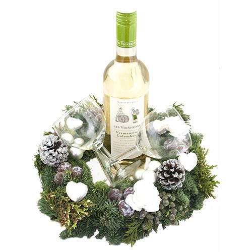 Fles witte wijn met gedecoreerde kerstkrans en twee wijnglazen