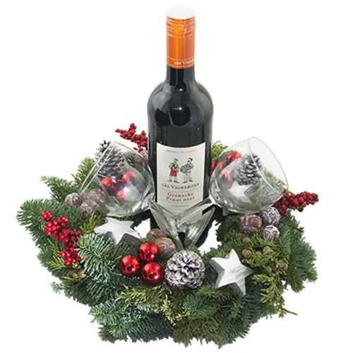 Fles rode wijn met gedecoreerde kerstkrans en twee wijnglazen